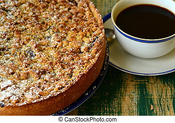 Plum crumble tart with cup of coffee on green background.