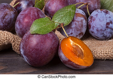 plum on the wooden background with sackcloth