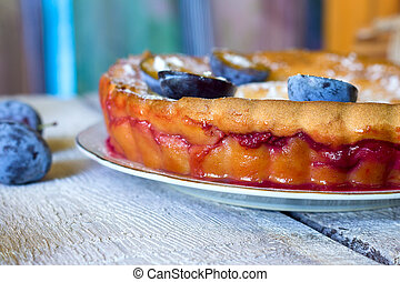 plum pie or tart and plums on rustic background.