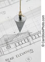 Plumb bob on architectural drawing.