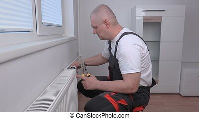 Plumber adjusting radiator and thinking