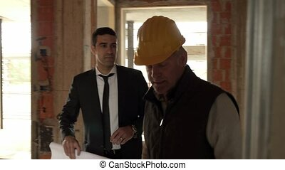 Apartment plumbing system and professional jobs, plumber and engineer talking and looking at building plans in construction site. Steadicam shot