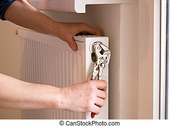 plumber and radiator - plumber fixing a radiator with pliers...