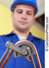 Plumber bending copper pipe