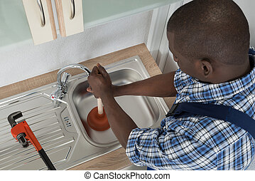 Plumber Cleaning Sink With Plunger