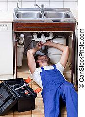 Plumber during repairing sink