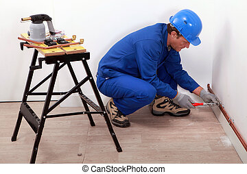 Plumber fitting copper pipes to a wall