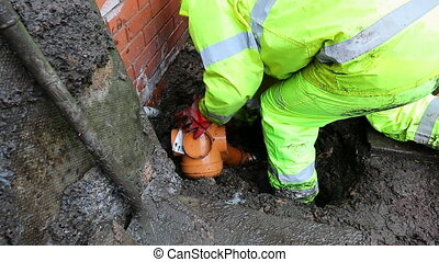Professional plumber in bright waterproof clothing is working outside the house. He is fitting a new drainage bottle gully onto the pipe in the ground.