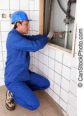 Plumber fixing a pipe to a wall