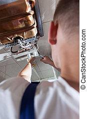 Plumber fixing gas water heater