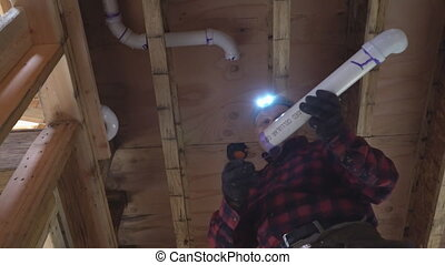 Plumber Fixing glued plastic toilet white pipe in close-up...