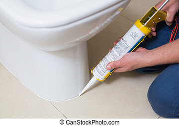 Plumber fixing toilet in a washroom with silicone cartridge...