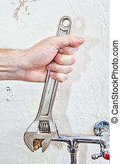 Plumber hands fixing water tap valve with plumbing ...