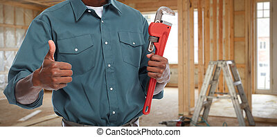 Plumber hands with a pipe wrench .