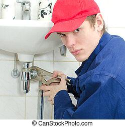 Plumber in uniform repairing old pipeline in the house.