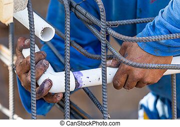 Plumber Installing PVC Pipe at Construction Site