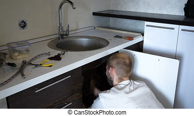 Plumber installs the crane - Plumber locks the faucet in the...