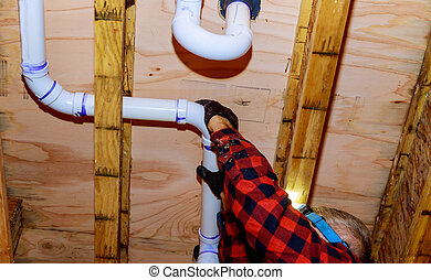 Plumber putting glue on a pvc pipe, plumber joining plastic pipes with cement for renovation new home construction