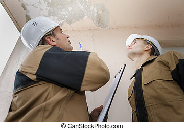 plumber looking at a ceiling leak