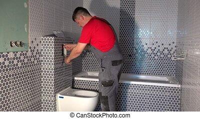 Plumber man draw water from pipe of toilet flushing...