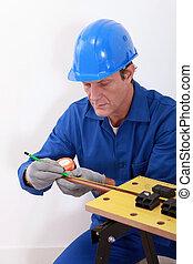 Plumber measuring copper pipe
