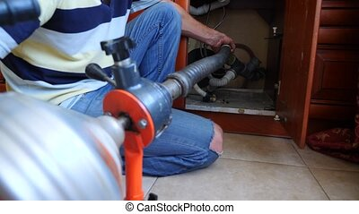 Plumber pipeline repairs in the house. Close-up. The plumber cleans the pipes with equipment. 4k, slow motion.