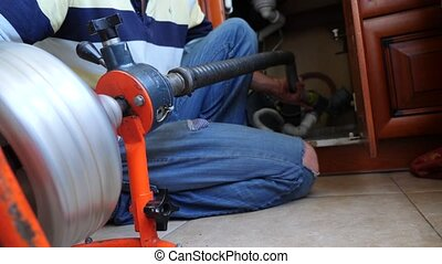 Plumber pipeline repairs in the house. Close-up. The plumber cleans the pipes with equipment. 4k, slow motion