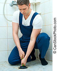 Plumber repairing bathroom with hand plunger.