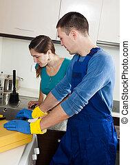 plumber repairing kitchen sink for  woman