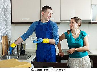 Plumber repairing  sink for happy woman