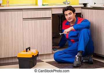 Plumber repairing  wash basin at kitchen