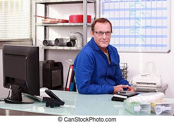 Plumber sat at desk