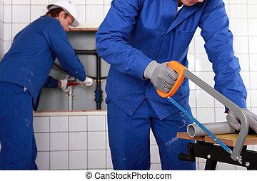 Plumber sawing grey pipe