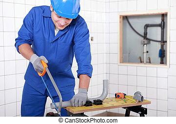 Plumber sawing plastic pipe