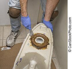 Plumber showing wax ring on toilet - Body shot of plumber ...