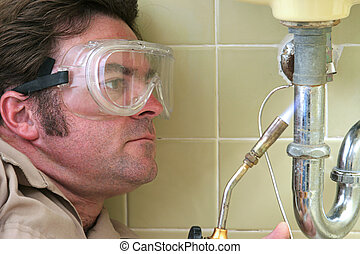 Plumber Soldering - A plumber using a welding torch to...