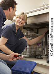 Plumber Teaching Apprentice To Fix Kitchen Sink In Home