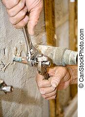 Plumber Tightens Valve - Closeup of plumbers hands using...