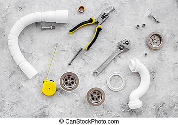 Plumber tools on grey stone background top view