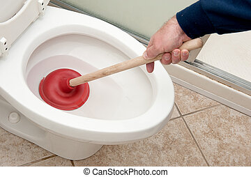 Plumber unclogging toilet - A plumber uses a plunger to...
