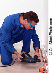 Plumber using a drill to install copper pipes