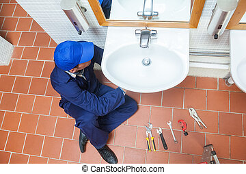 Plumber with cap repairing sink