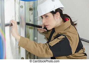 plumber woman builder fixing heating system pipes