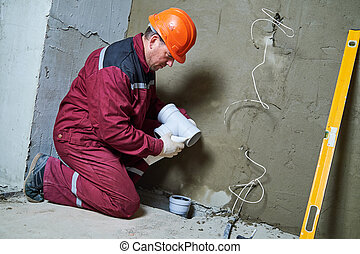 Plumber worker installing sewage pipes in sewerage system