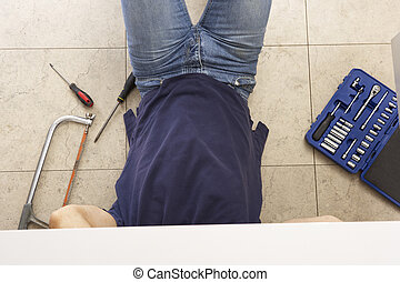 Plumber Working On Sink In Kitchen