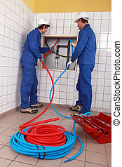 Plumbers installing new hot and cold pipes