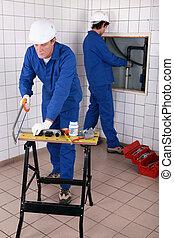 Plumbers installing water pipes