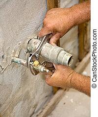 Plumbing Closeup - Closeup of plumbers hands tightening a...