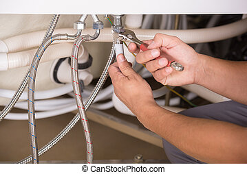 Plumbing - Hands repairing the plumbing pipes of an electric...