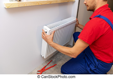 plumbing services - plumber installing heating radiator on the wall